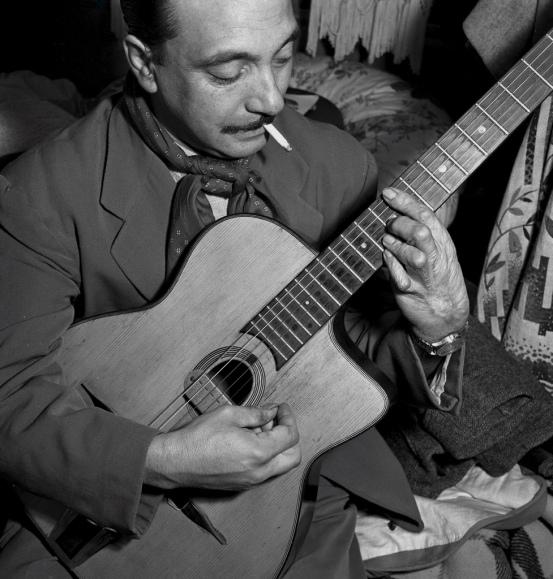 """Le Bourget, novembre 1950 : les reporters de """"Paris Match"""" partent ‡ la rencontre de Django REINHARDT, le cÈlËbre guitariste de jazz manouche qui, actuellement, campe dans sa roulotte au Bourget o˘ il s'est installÈ avec ses proches. Ce gitan, aprËs avoir eu la main gauche br˚lÈe dans l'incendie de sa roulotte en 1928, est devenu l'un des rois du jazz. Django jouant de la guitare dans sa roulotte, cigarette ‡ la bouche."""